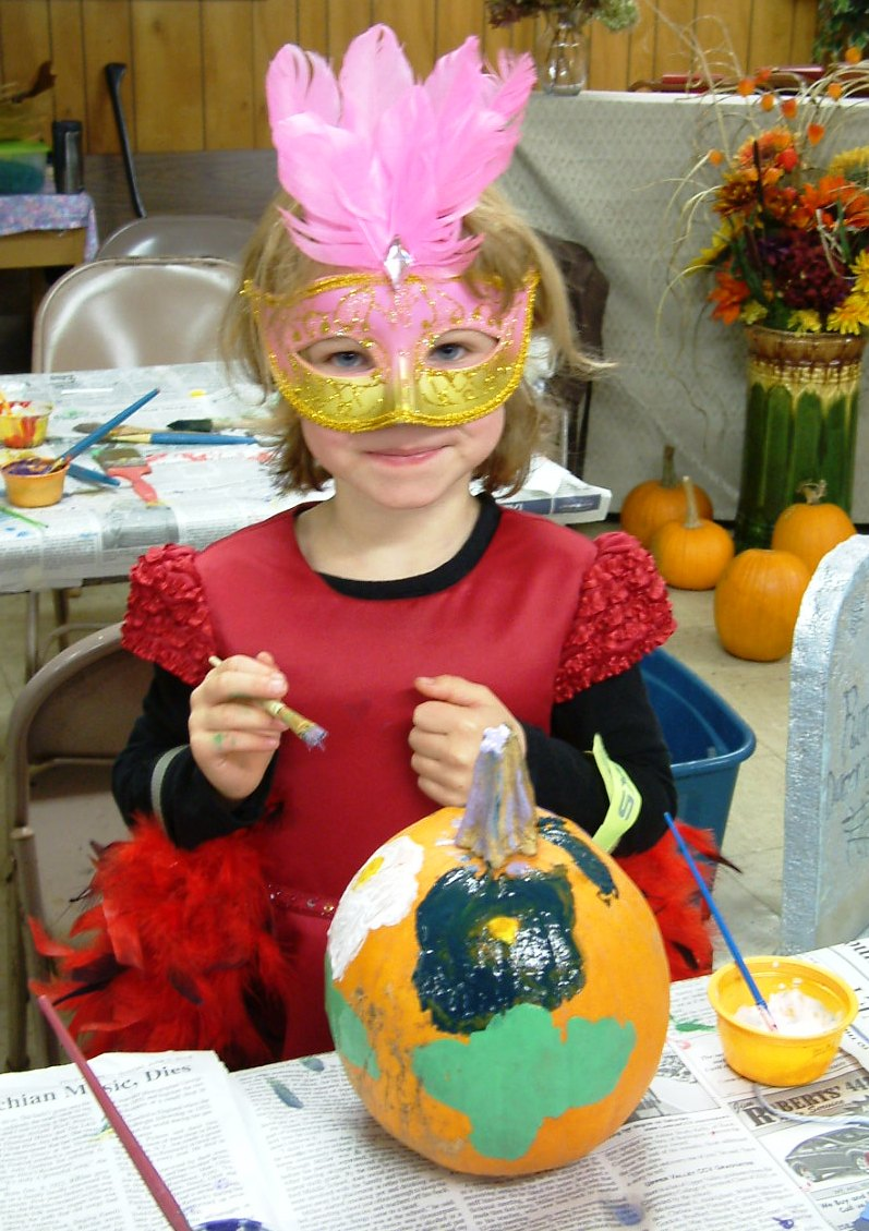 child in costume pumpkin painting